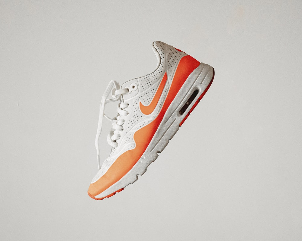 white and red nike athletic shoe