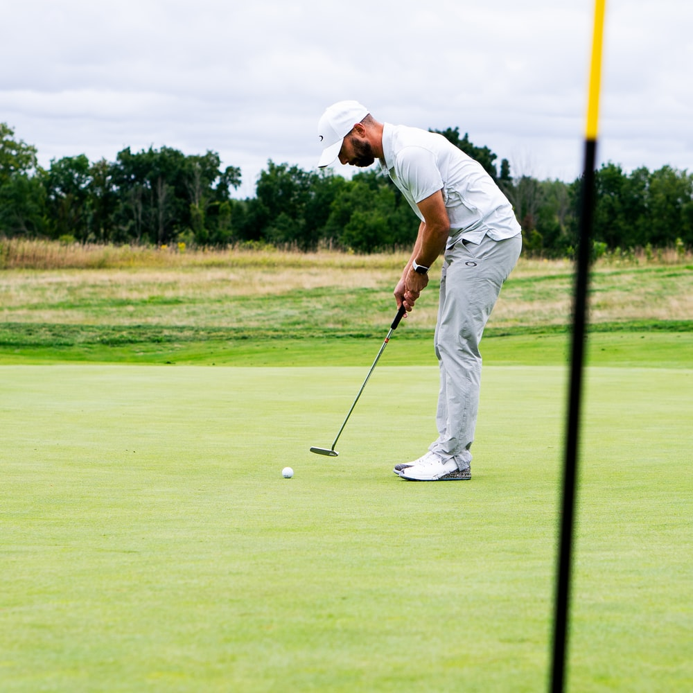 man in white shirt and white pants playing golf during daytime