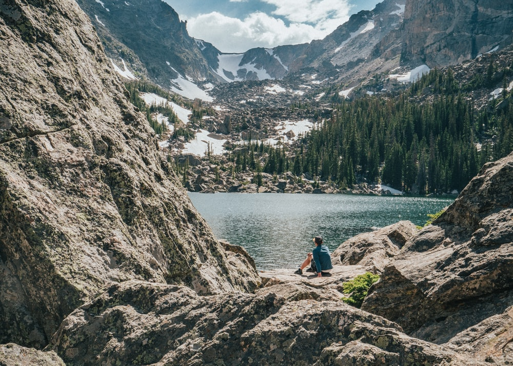 person sitting on rock near lake and mountain range