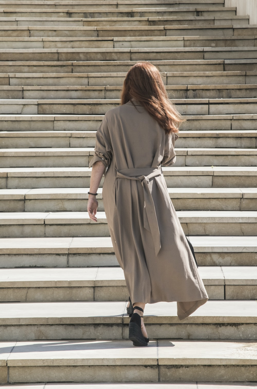 woman in brown long sleeve dress walking on white concrete stairs
