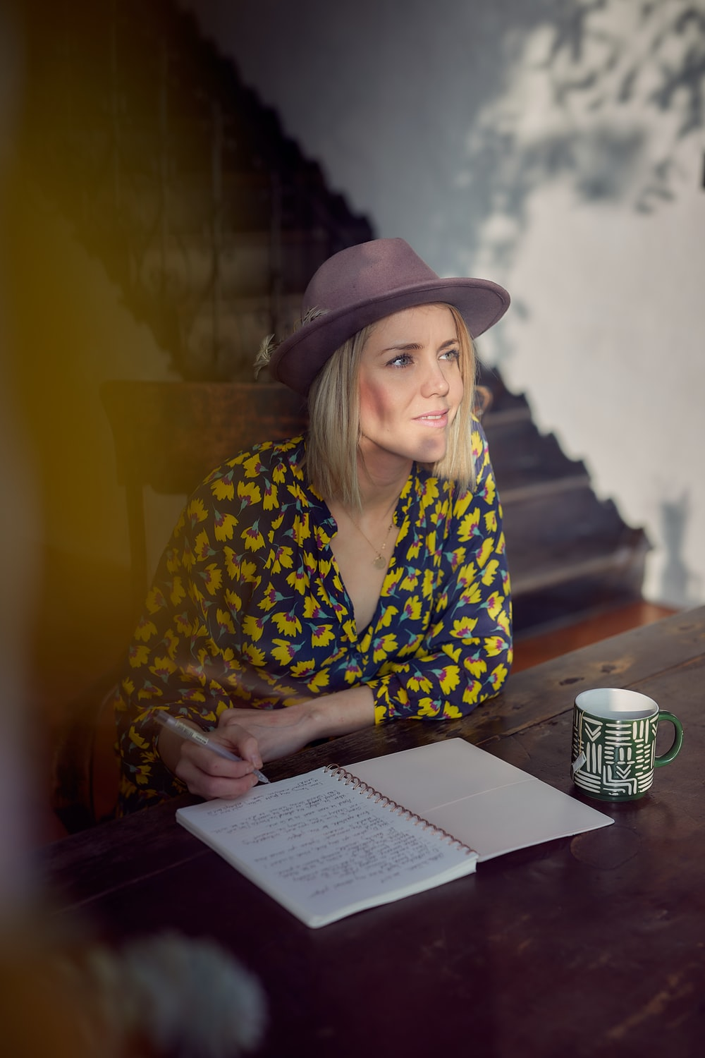 woman in blue and yellow floral long sleeve shirt wearing brown fedora hat