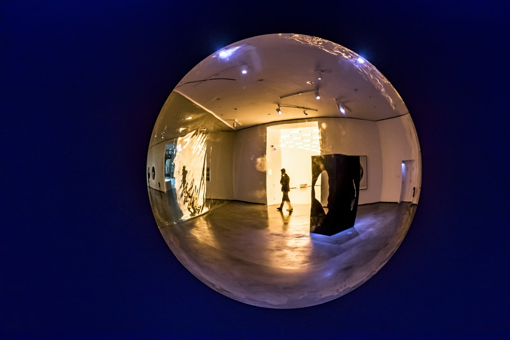 clear glass ball with reflection of man standing on the floor