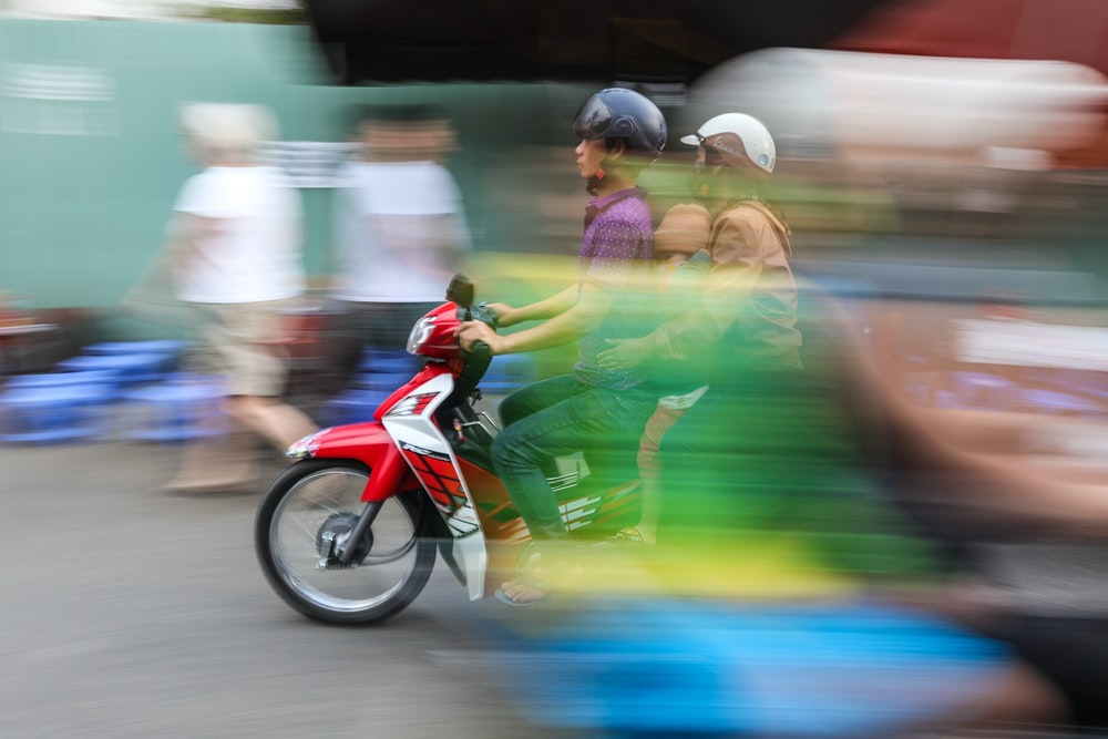 man in green shirt riding red motorcycle