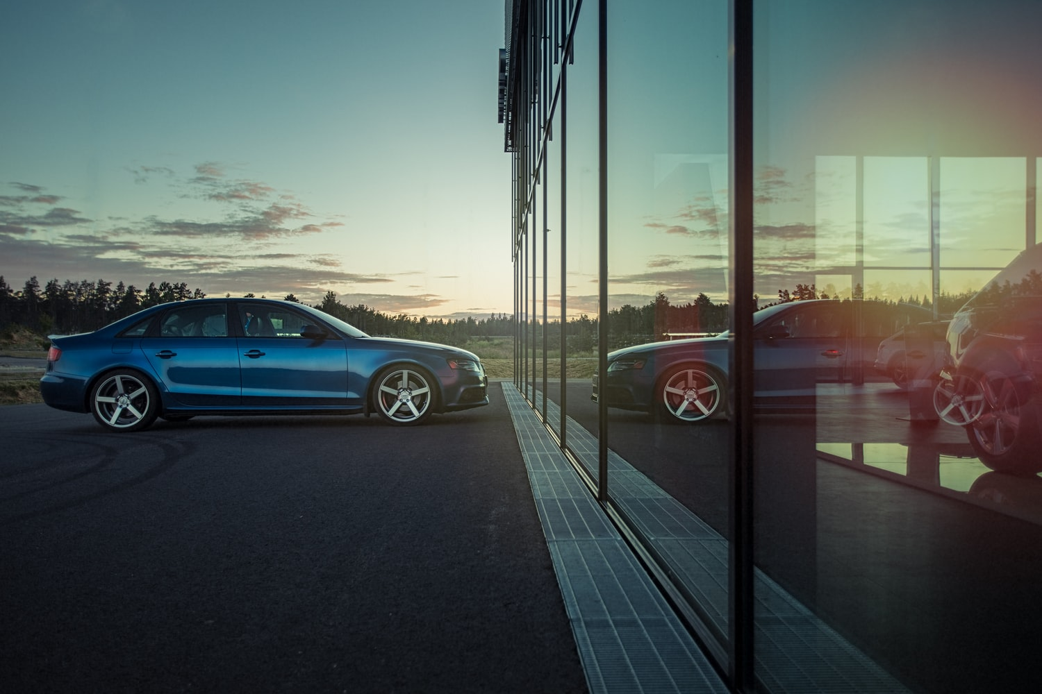Audi A4 in front of a mirrored window.