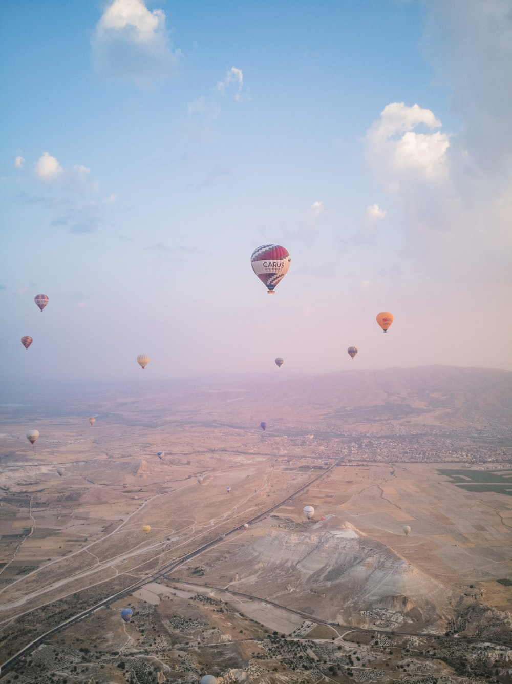 hot air balloons flying over the field during daytime