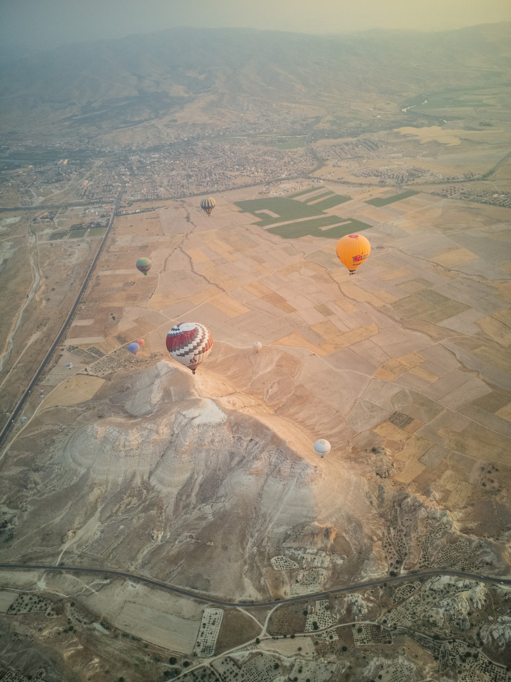 aerial view of hot air balloons on green grass field during daytime
