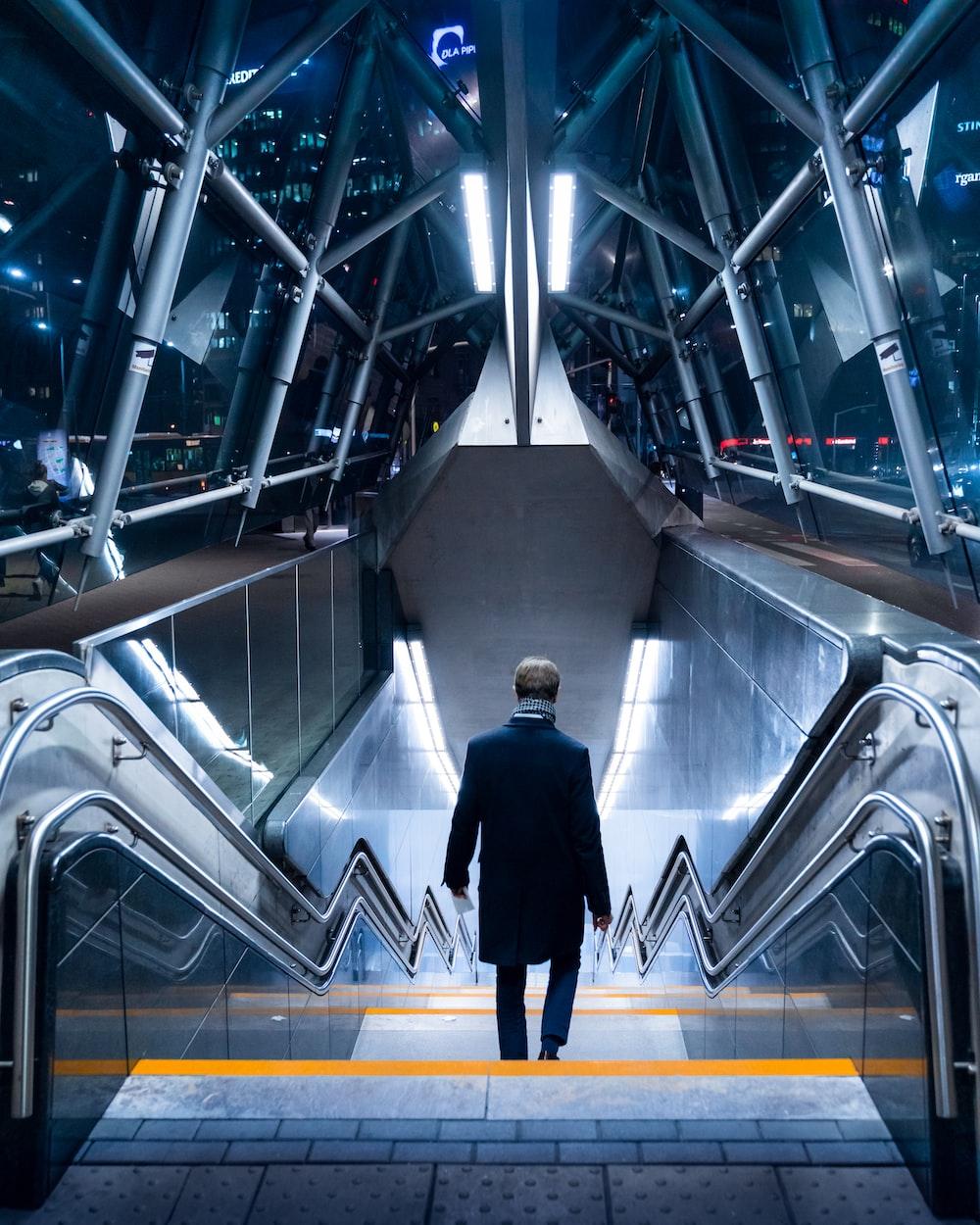 man in black suit walking on escalator