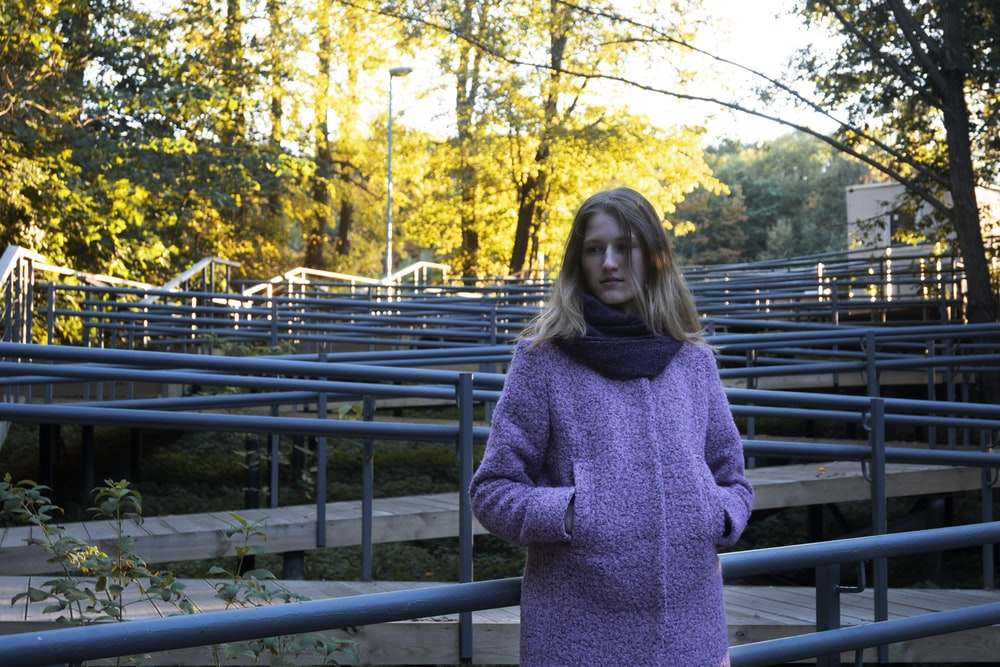 woman in gray sweater standing on bridge during daytime