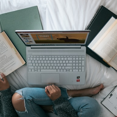 person in blue denim jeans sitting on bed with macbook pro