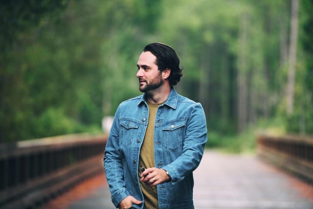 man in blue denim jacket standing on road during daytime