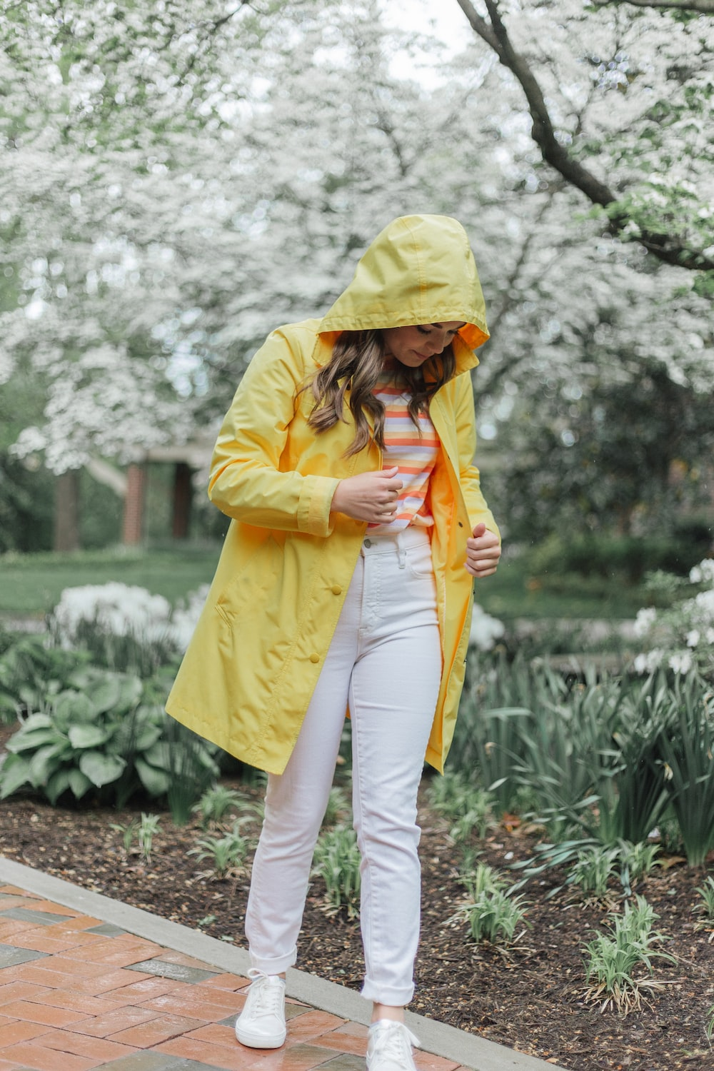woman in yellow hoodie and white pants holding yellow umbrella