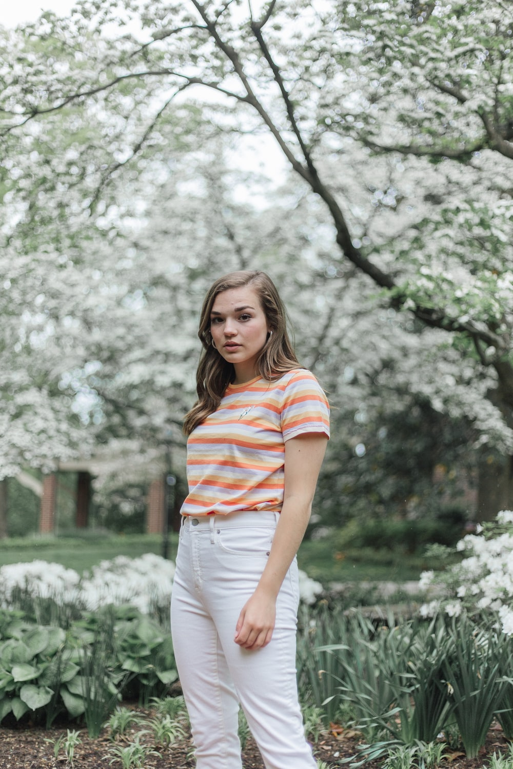 woman in white and red striped shirt standing near trees during daytime