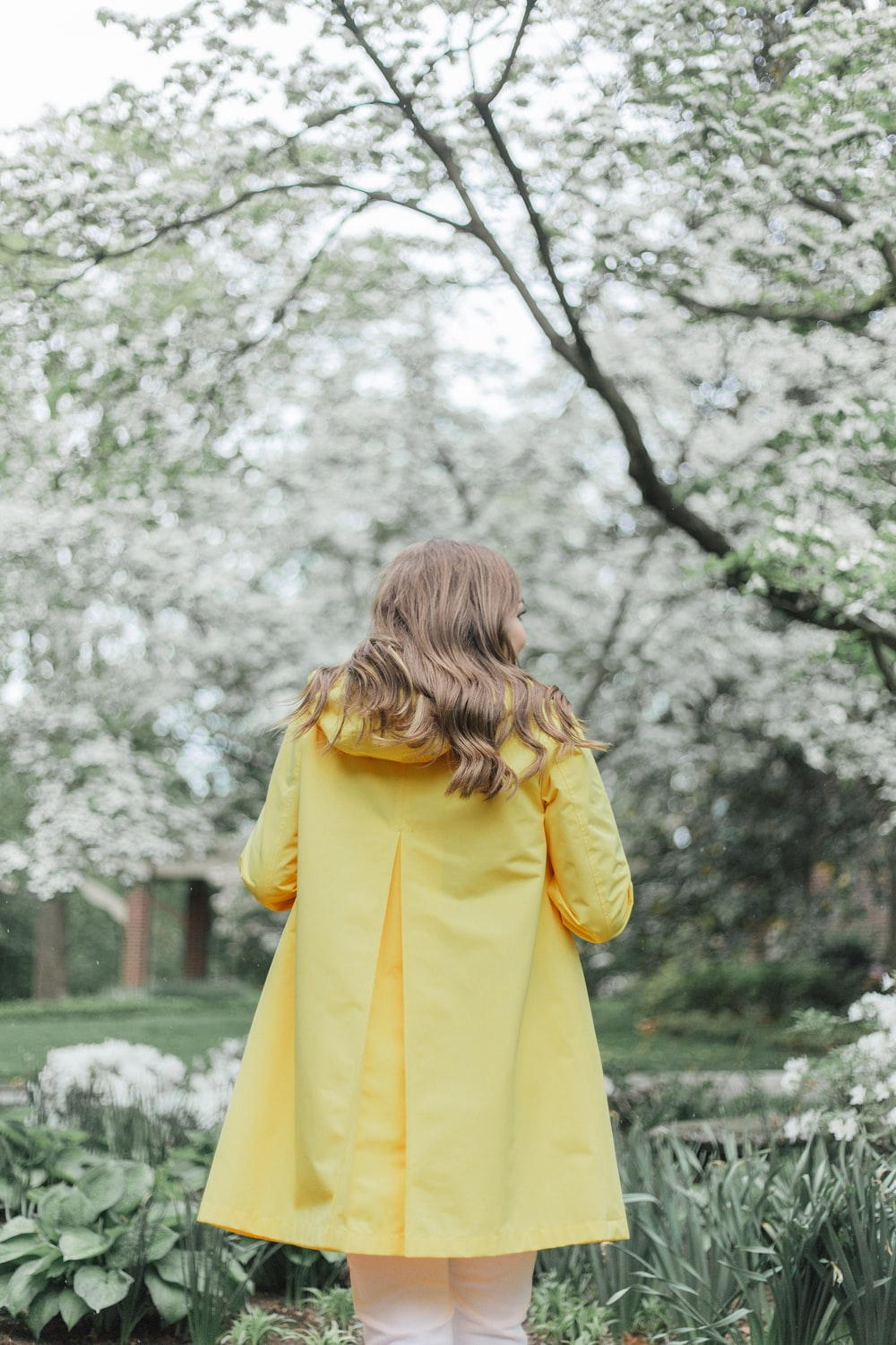 woman in yellow coat standing near trees during daytime