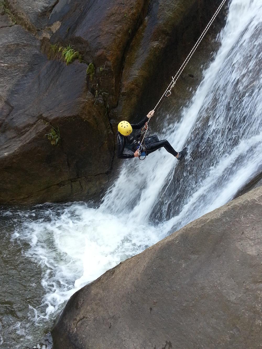 man in black jacket and black pants sitting on rock near waterfalls during daytime