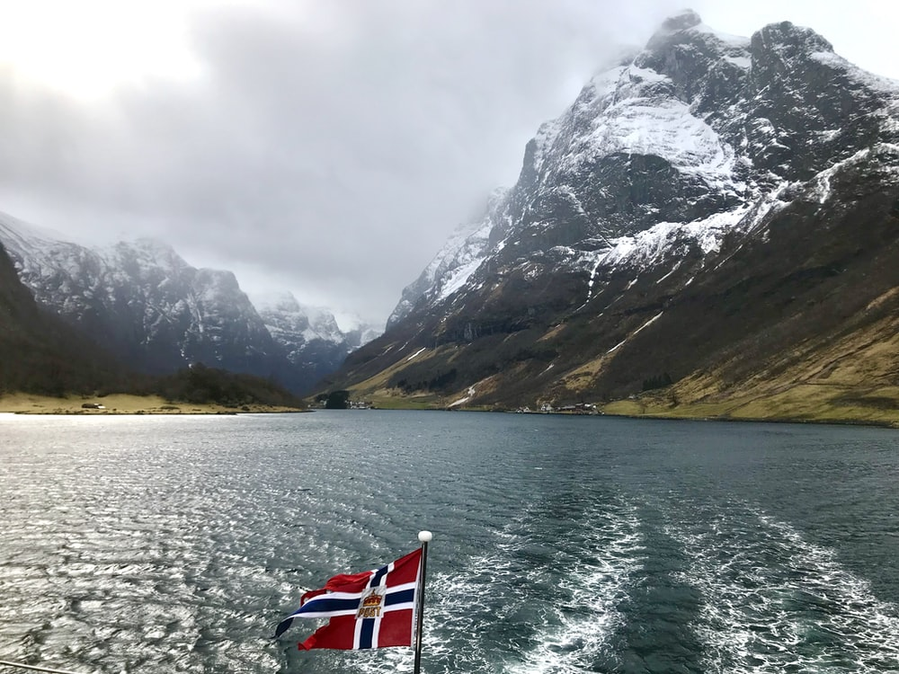 red and white boat on water near mountain during daytime