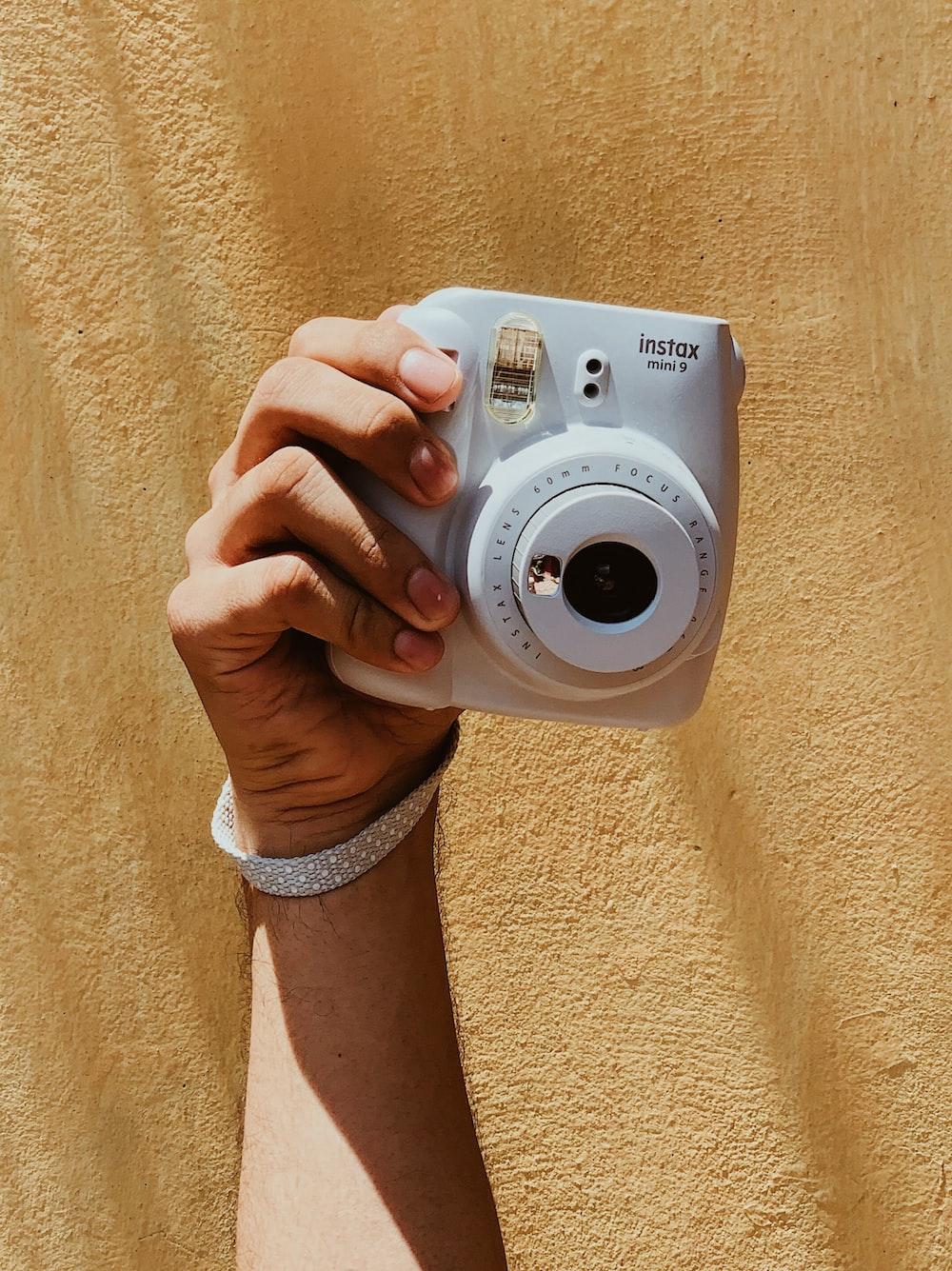 person holding white canon camera