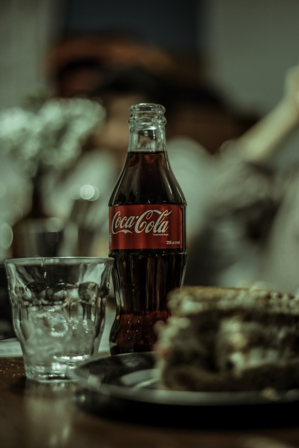coca cola bottle beside drinking glass