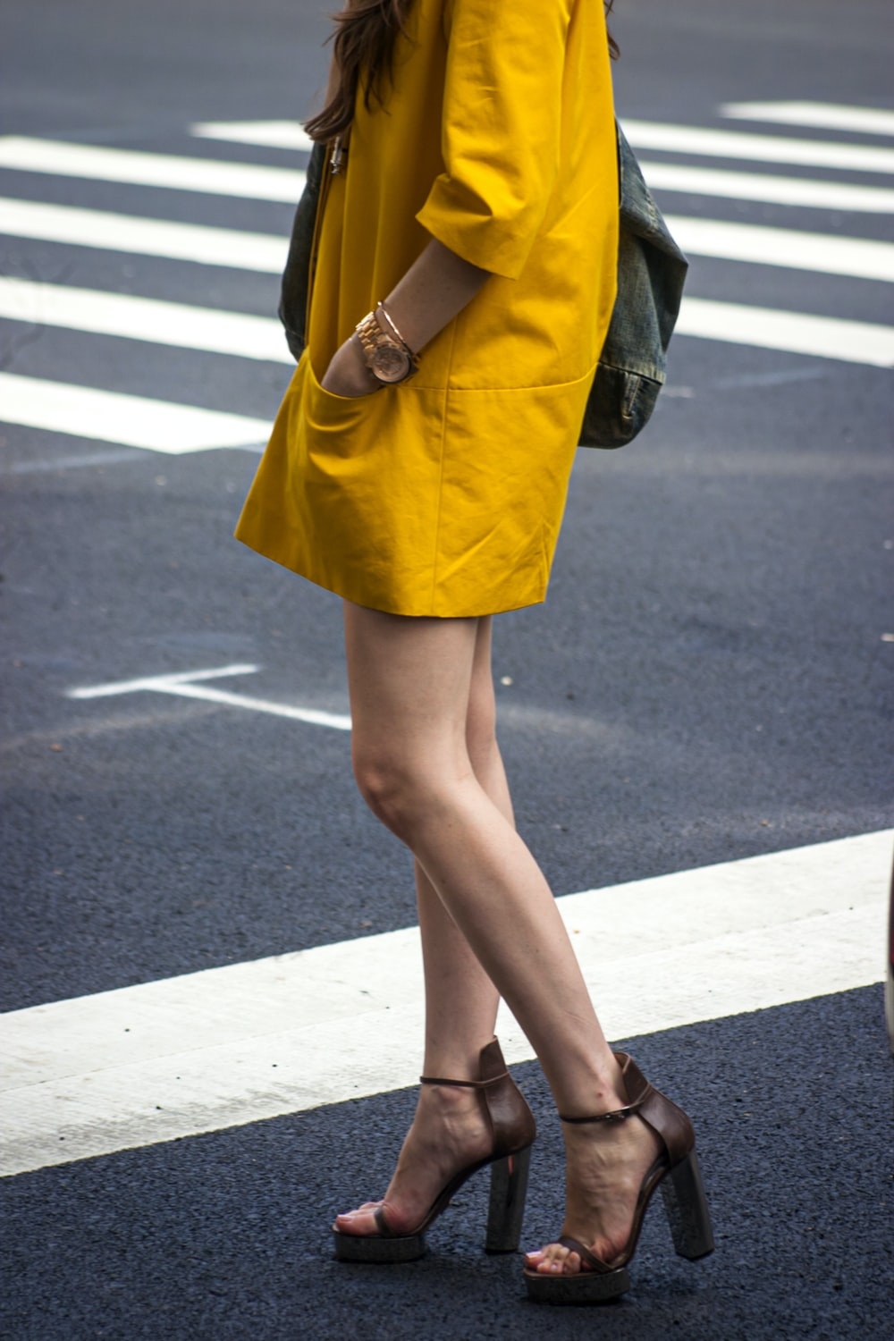 woman in yellow dress and black leather boots standing on gray asphalt road during daytime