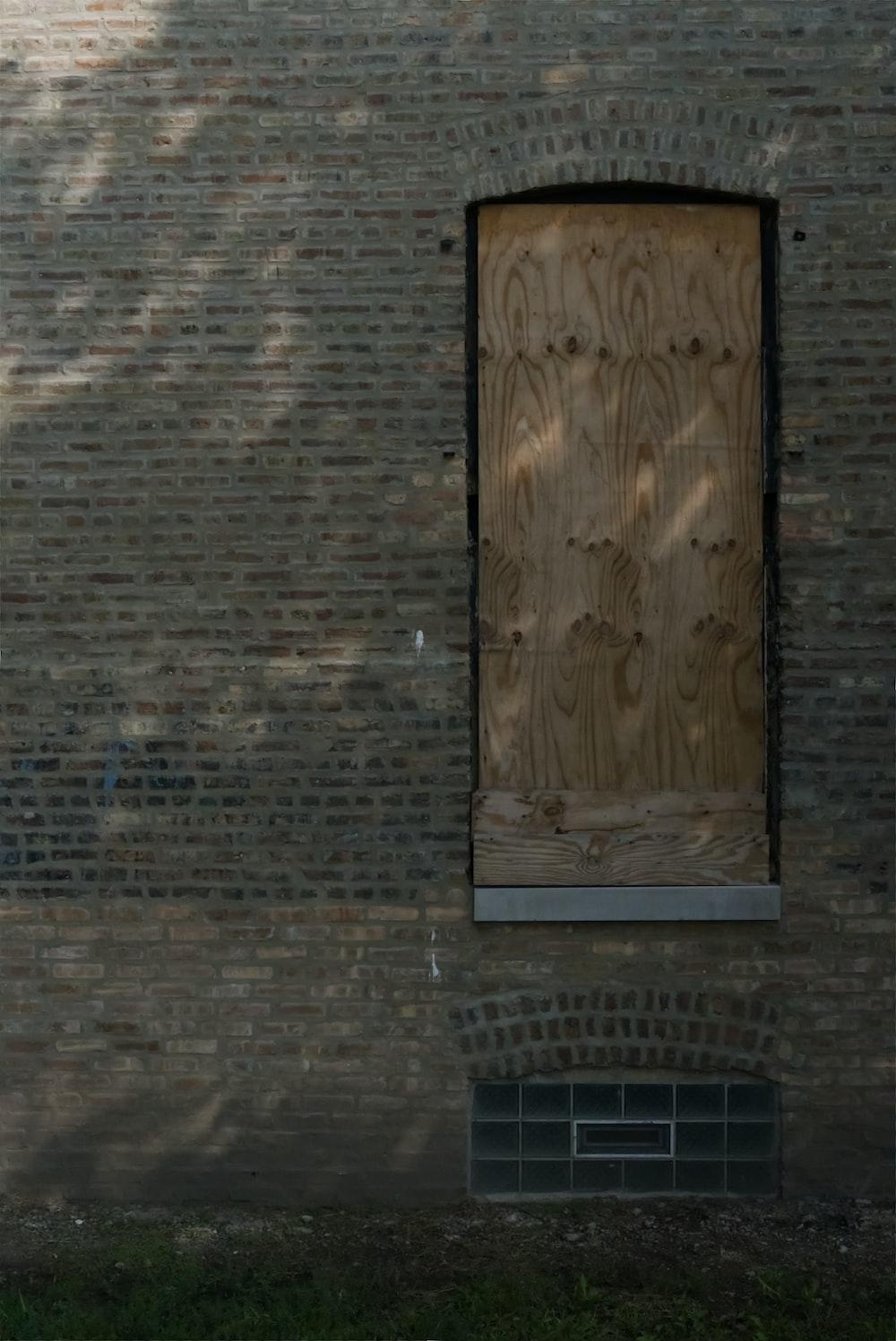 brown wooden door on brown brick wall