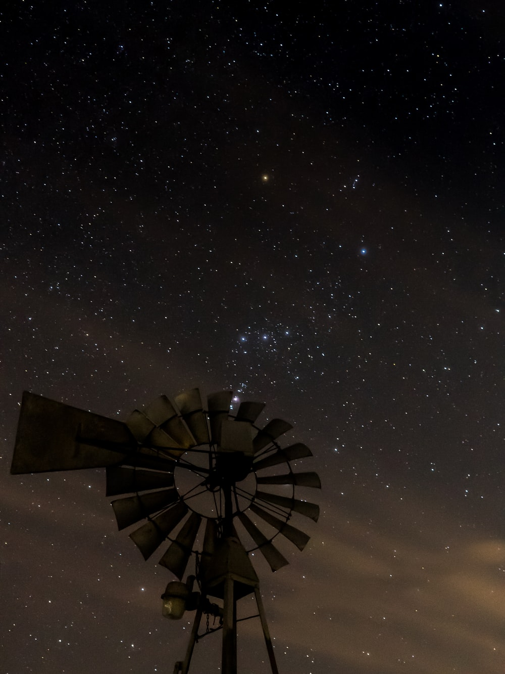 brown wooden windmill under starry night