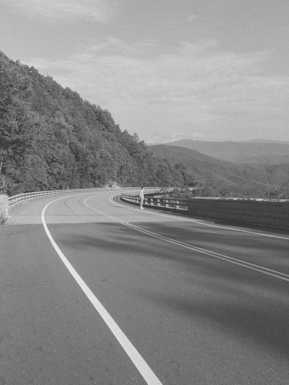 grayscale photo of road near mountain