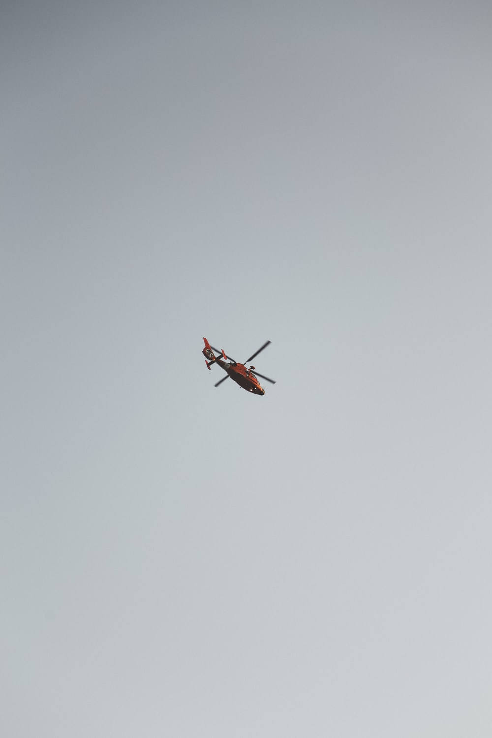 red and white helicopter in mid air