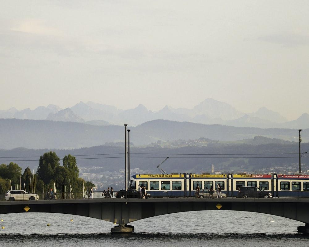 yellow and black train on bridge over river