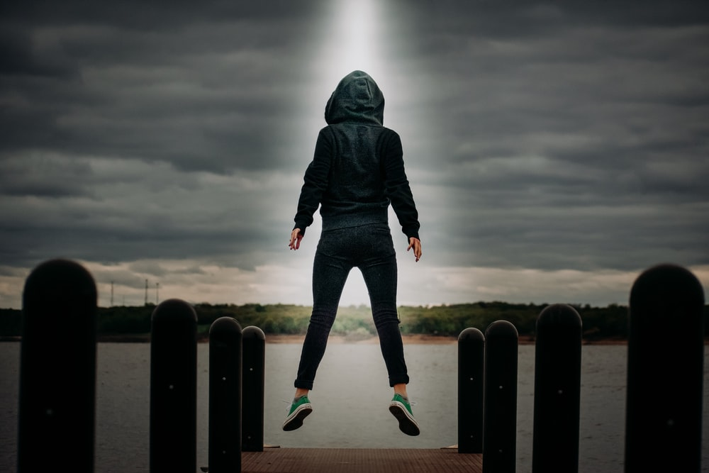 man in black hoodie and blue denim jeans standing on black metal fence under gray clouds