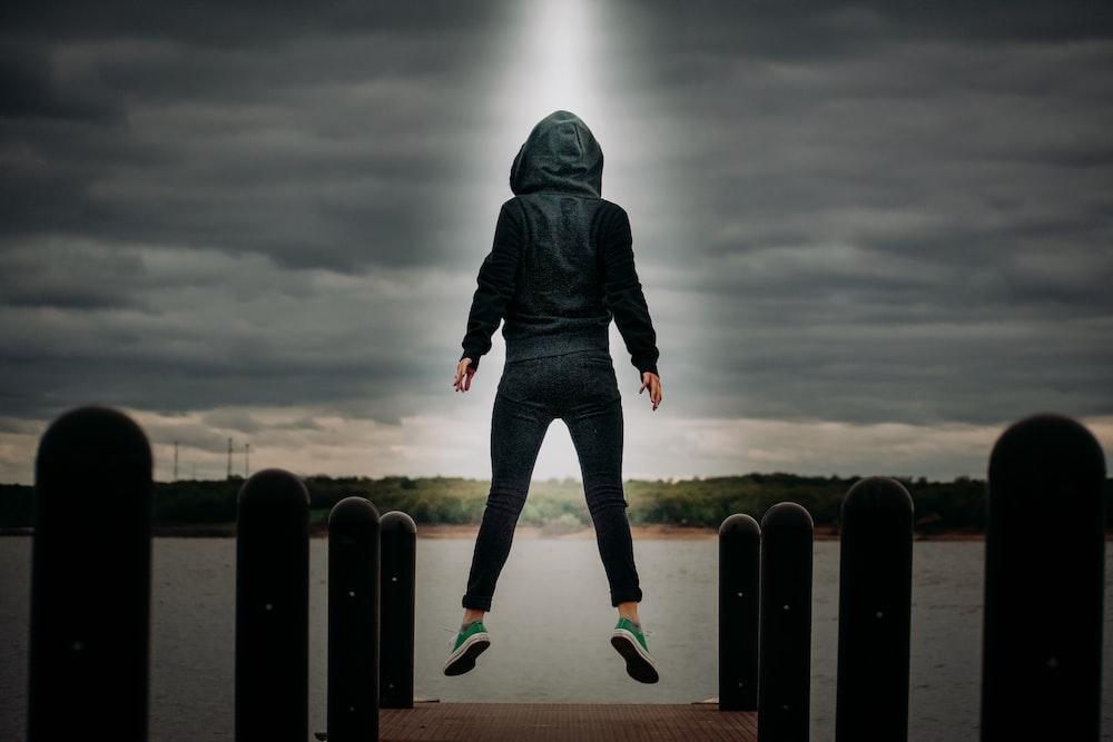 man in black hoodie and blue denim jeans standing on black metal fence under gray clouds