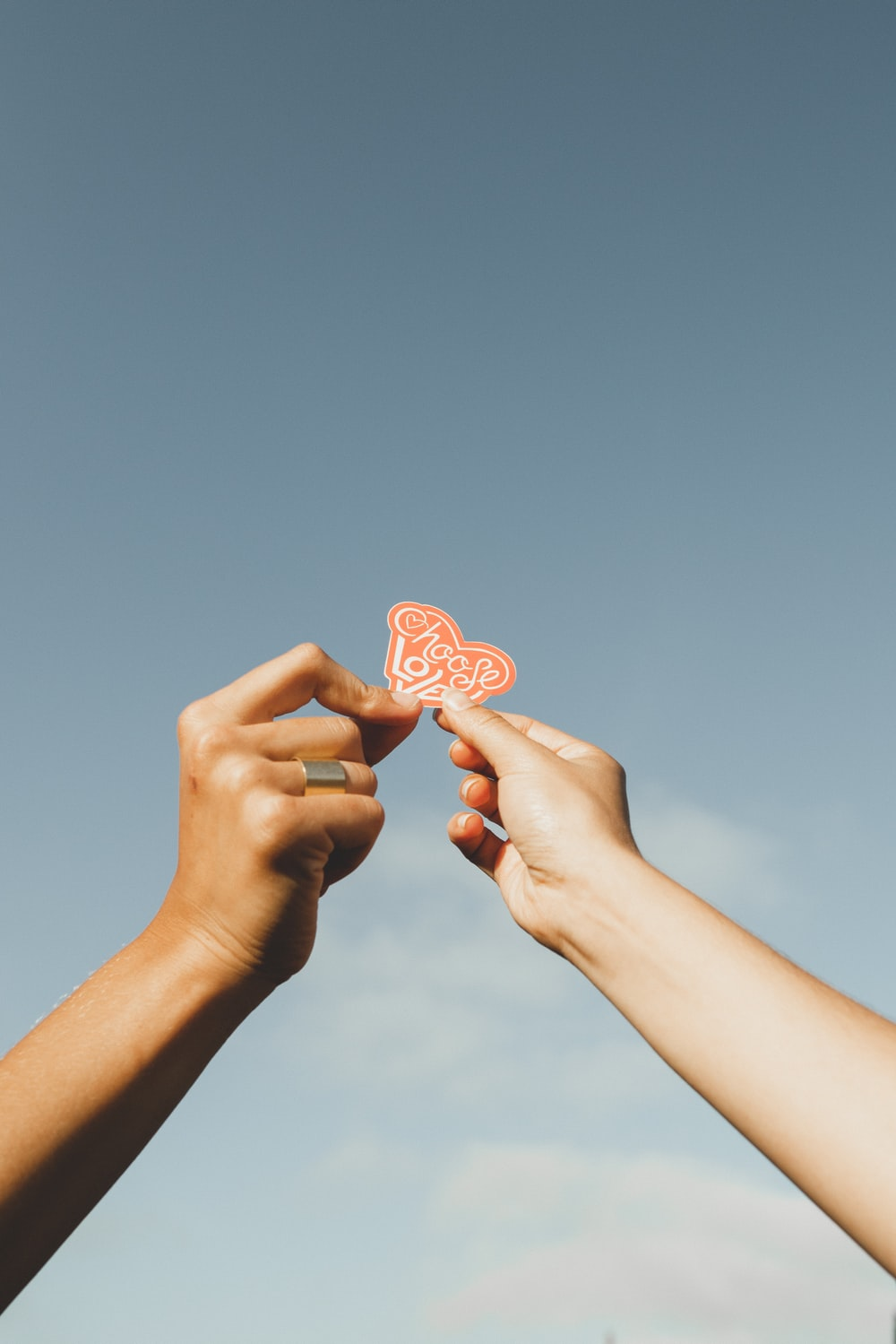 person holding pink heart shaped ornament