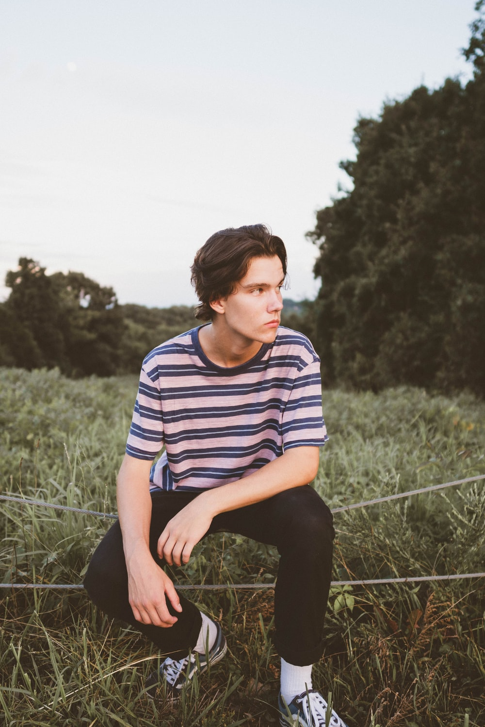 man in blue and white striped crew neck t-shirt sitting on grass field during daytime