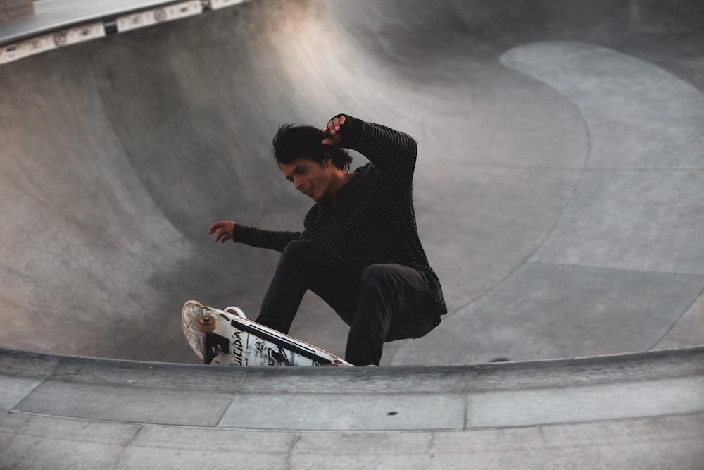 man in black long sleeve shirt and black pants sitting on skateboard