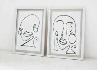 2 white wooden framed wall art