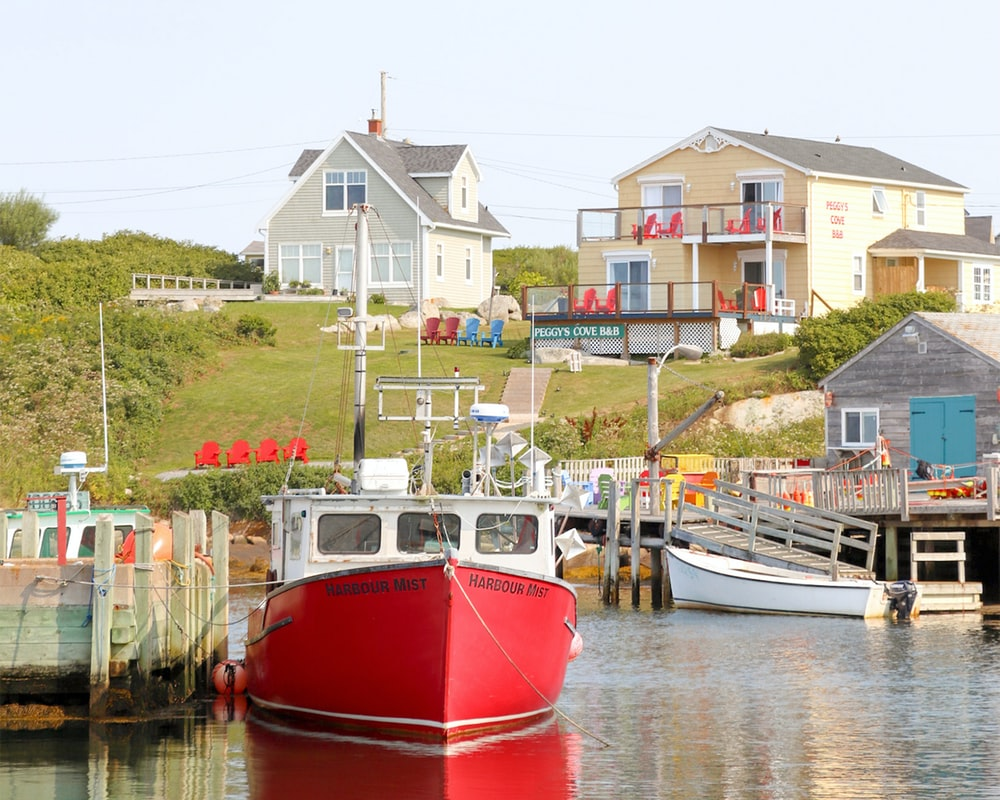 red and white boat on body of water near houses during daytime