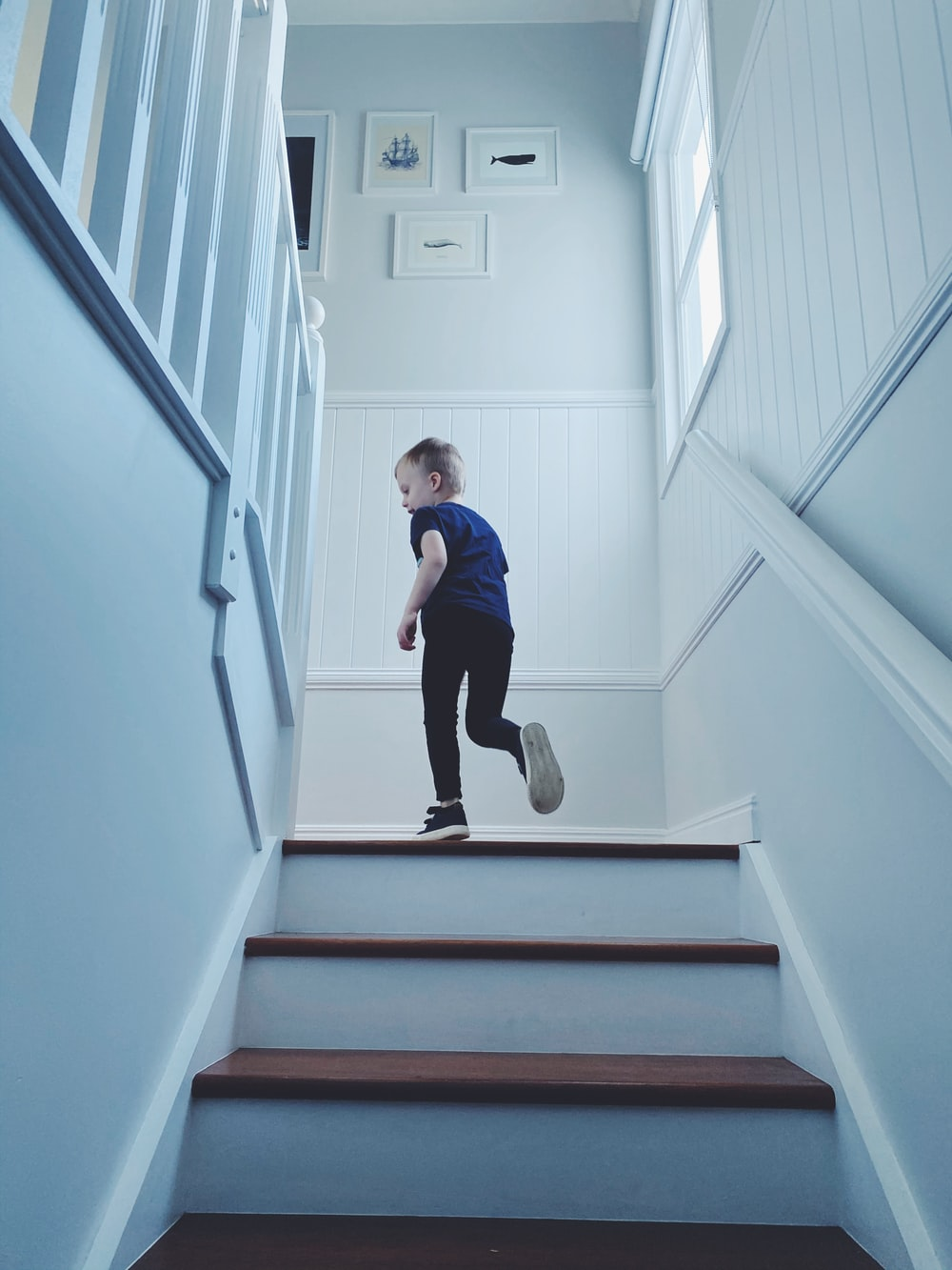 man in blue shirt and black pants sitting on white staircase