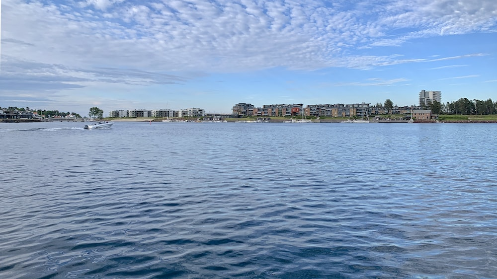 body of water near city buildings under blue and white sunny cloudy sky during daytime
