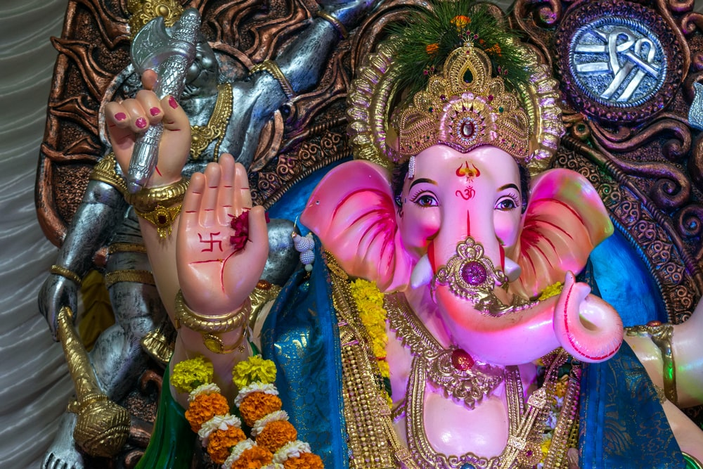 hindu deity figurine on blue textile