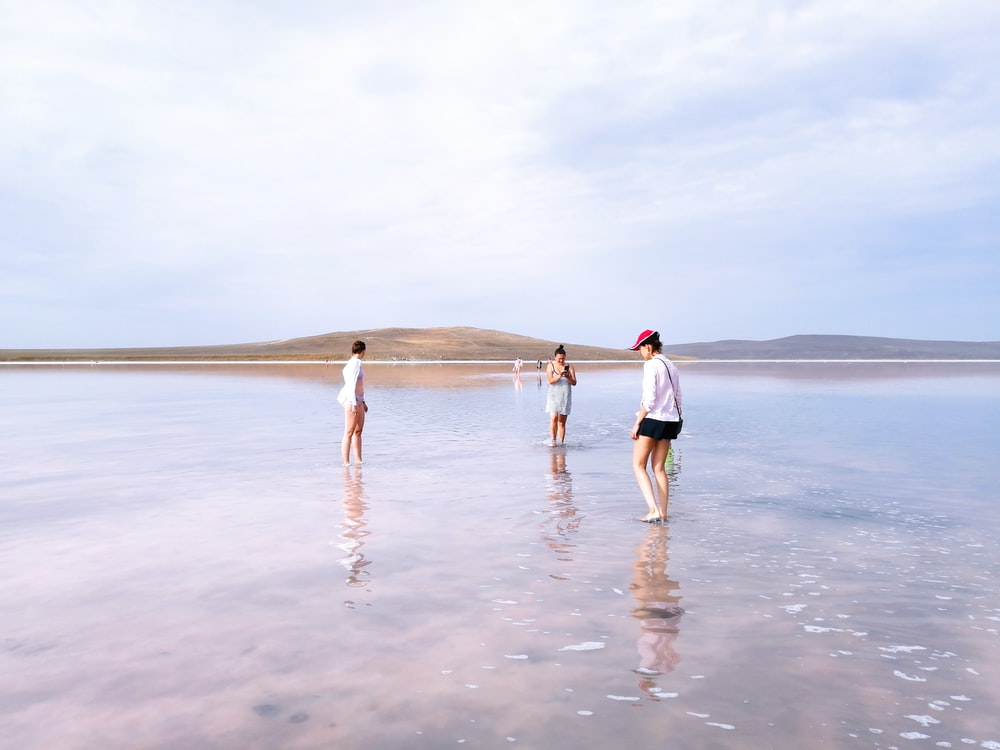 woman in white shirt and white shorts walking on beach during daytime