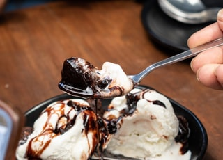 ice cream with chocolate syrup on brown wooden table