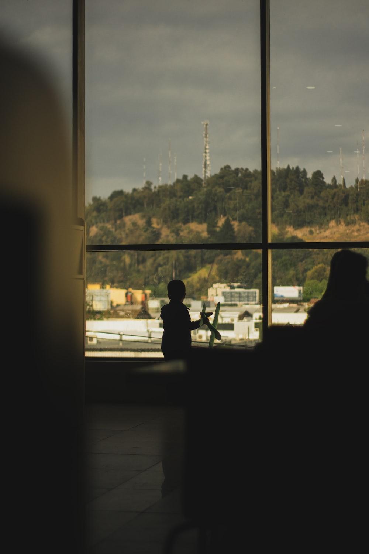 2 person sitting on chair near window