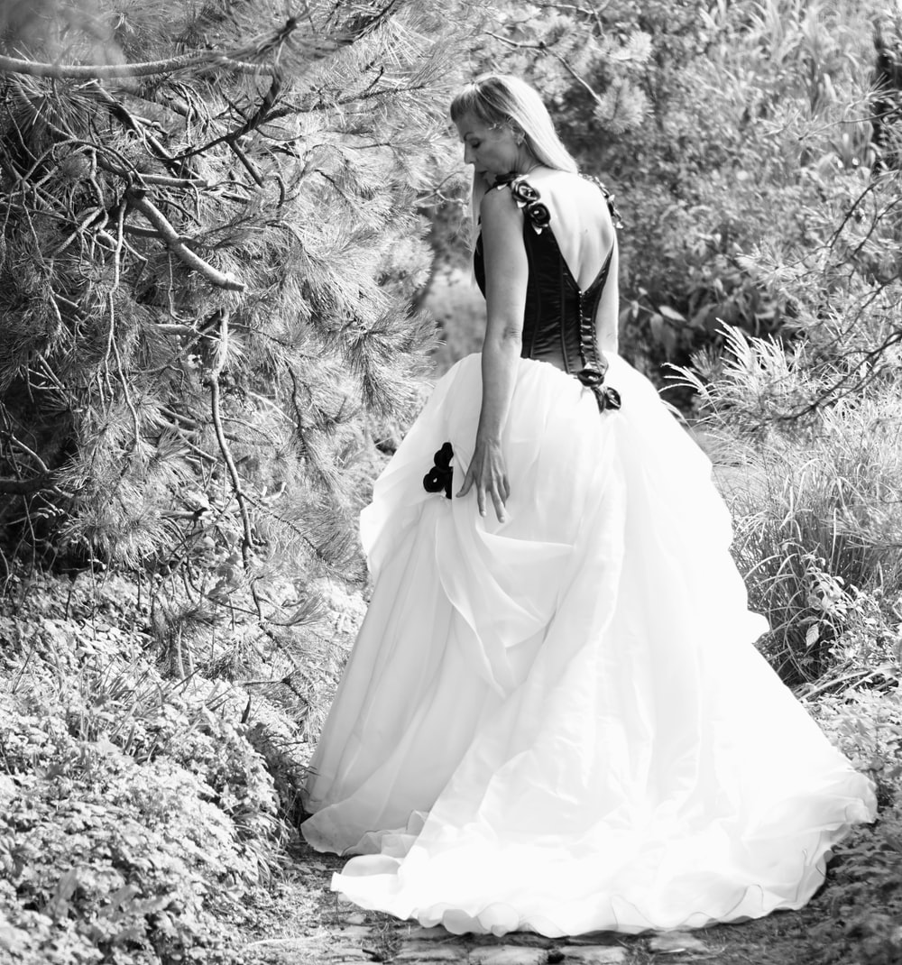woman in white wedding dress standing on the ground
