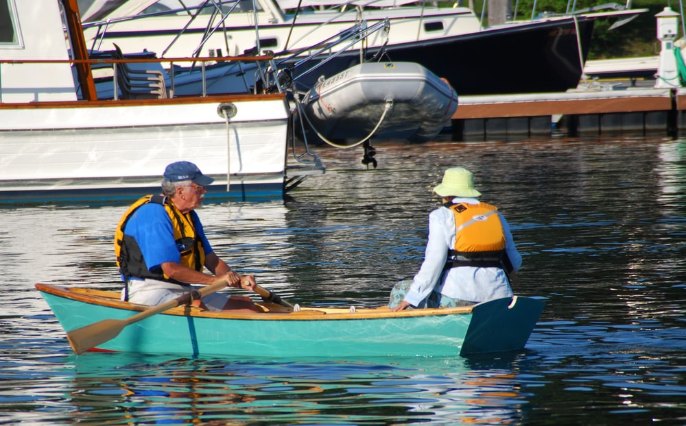 2 men in blue and yellow life vest riding on brown boat during daytime