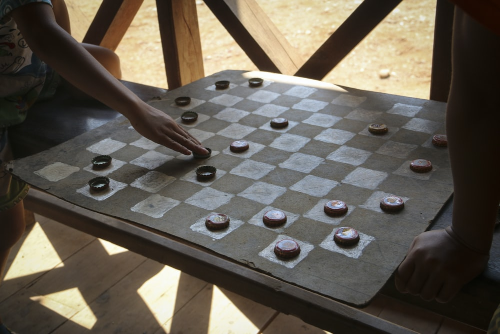 person holding black and white chess board game