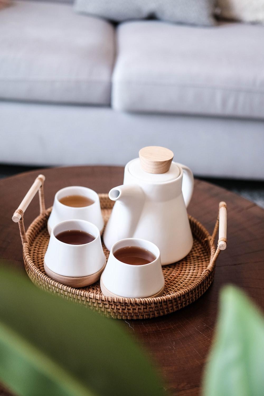 white ceramic mugs on brown woven basket