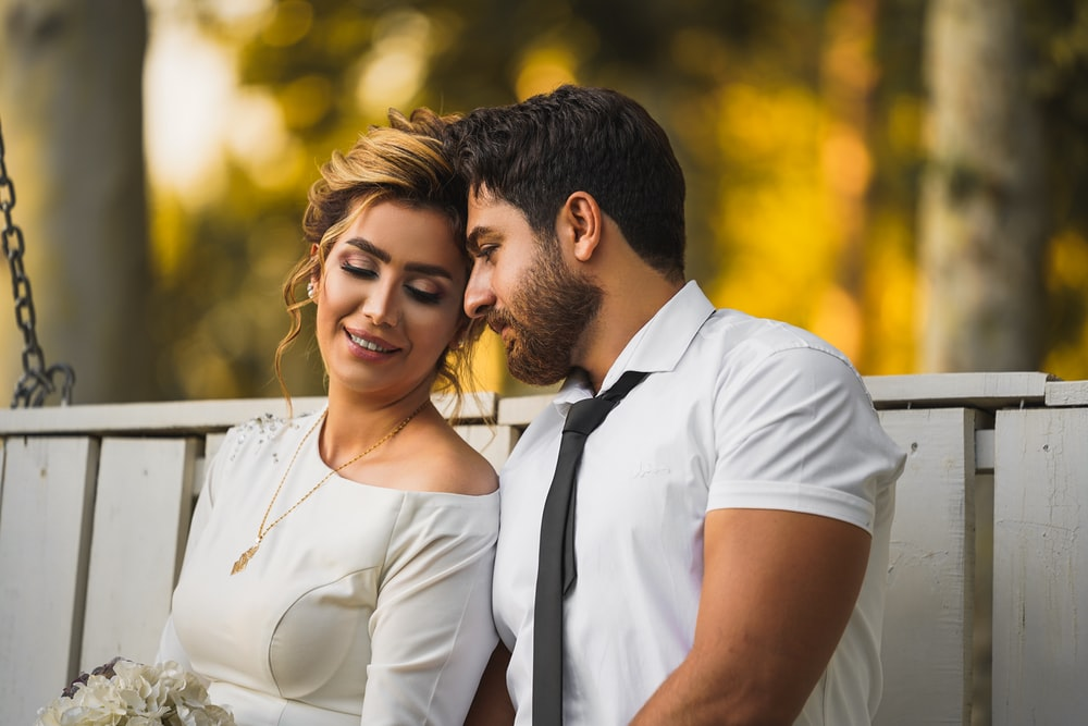 man in white dress shirt hugging woman in white dress