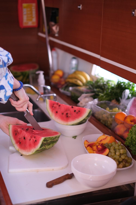 person slicing watermelon on white ceramic plate