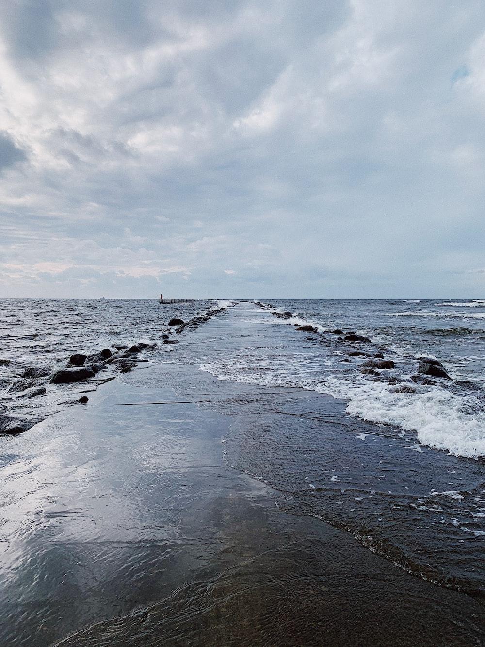 ocean waves crashing on shore under white clouds during daytime