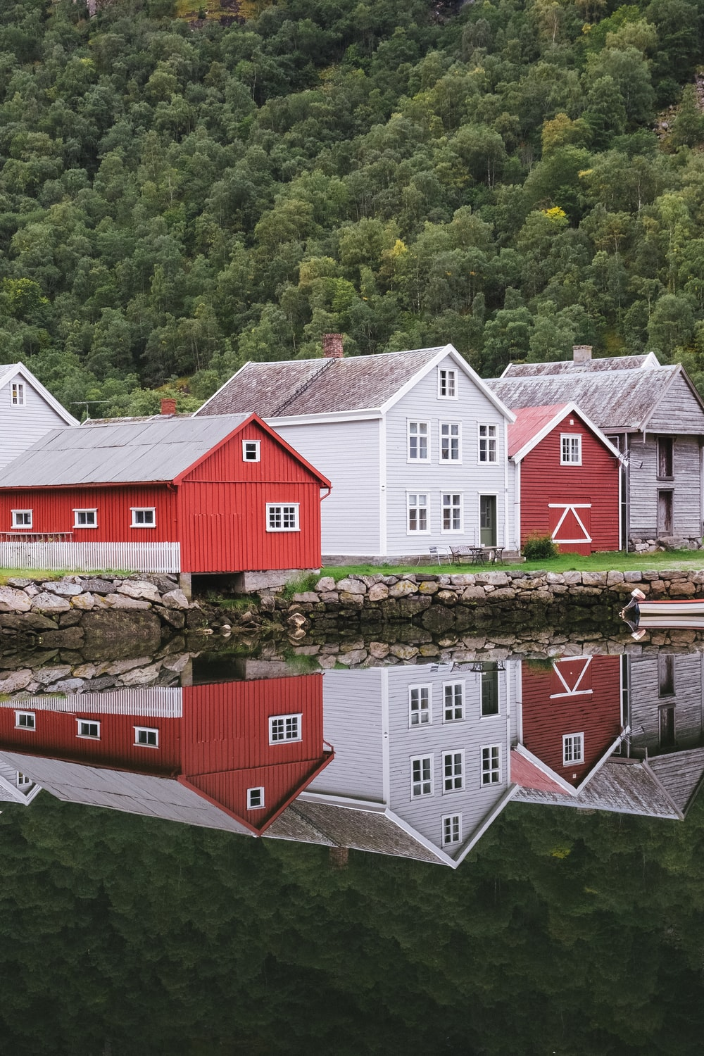 red and white wooden house beside river during daytime