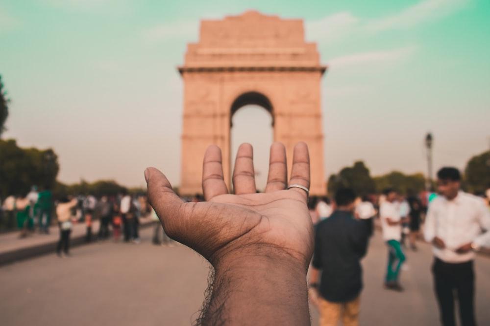 person holding brown concrete arch