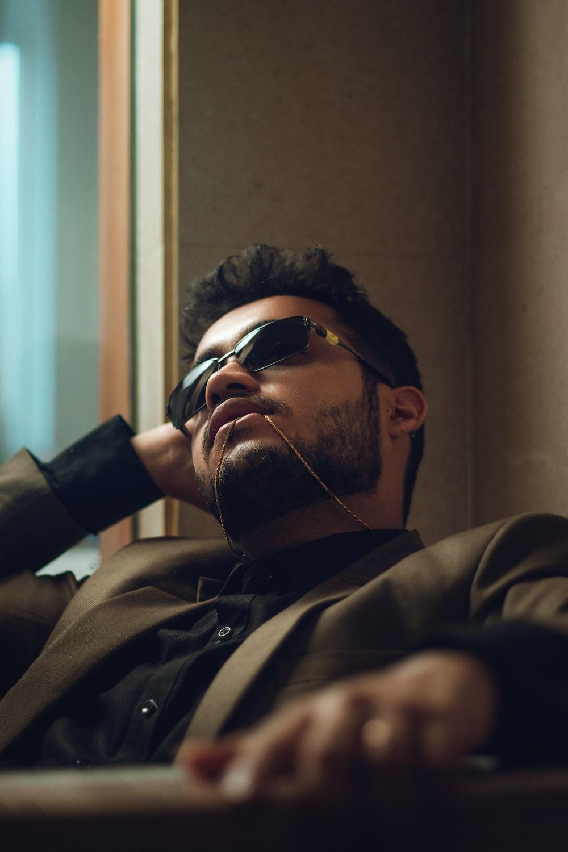 man in brown coat wearing black sunglasses
